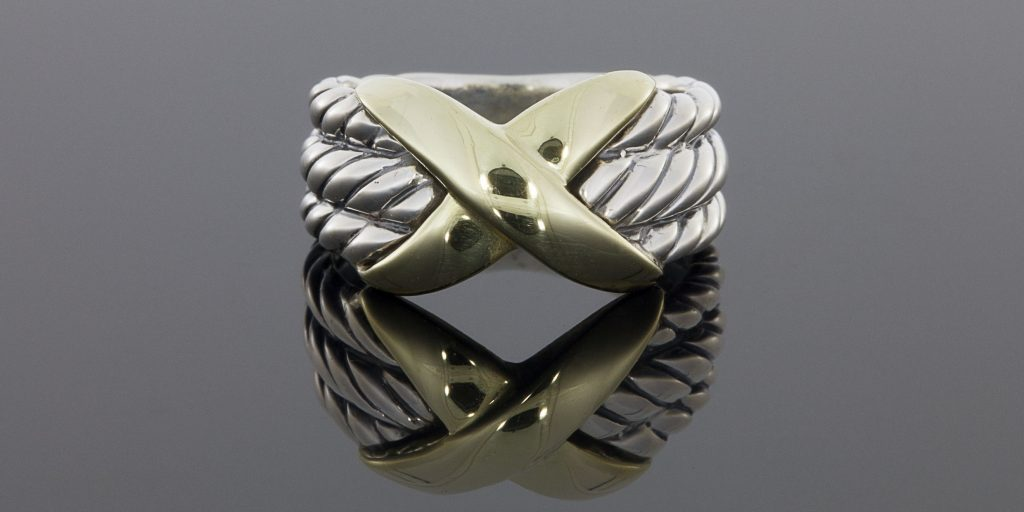 "This beautiful ring is from the Crossover Collection and features this signature cable design. It features 3 sterling silver, cable designed rows with a yellow gold ""X"" in the center. The ring measures 11mm wide at the top, tapering to 5mm at the base. It is currently a finger size 6.25 and is sizable upon request. We bought this for $75."